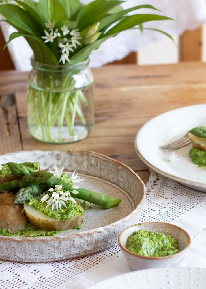 Wild Garlic Pesto Foraged and Vegan on potatoes and asparagus with a jar of wild garlic in the background
