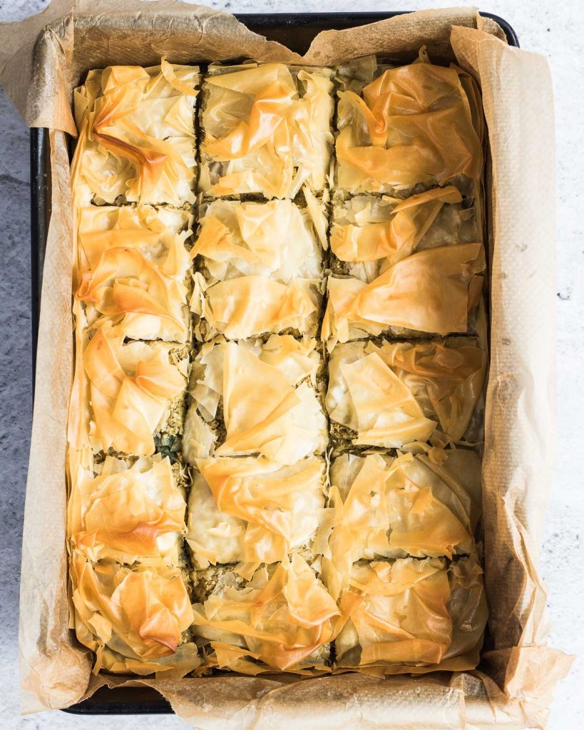 Whole spanakopita pie ready to be eaten. It's been cut up into squares in the tin.