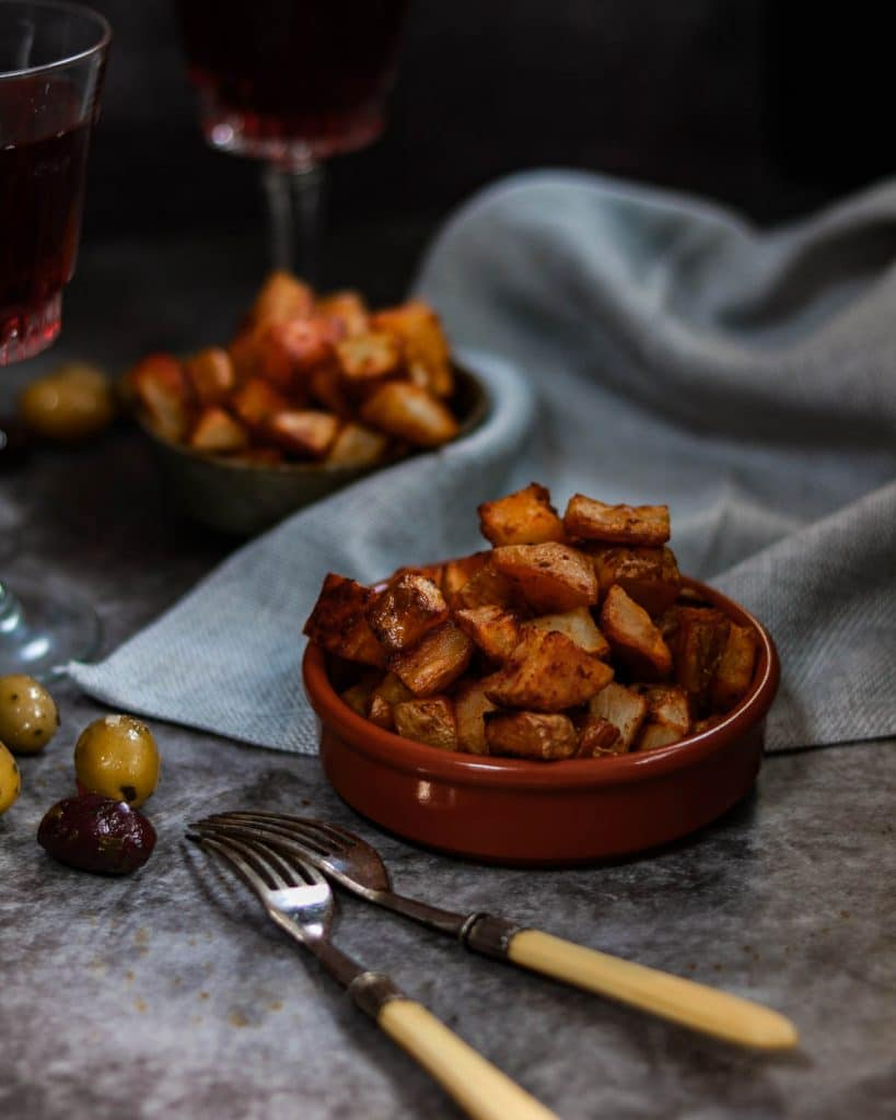 Plain oven baked patatas bravas in a bowl with olives and glasses of wine in the background.