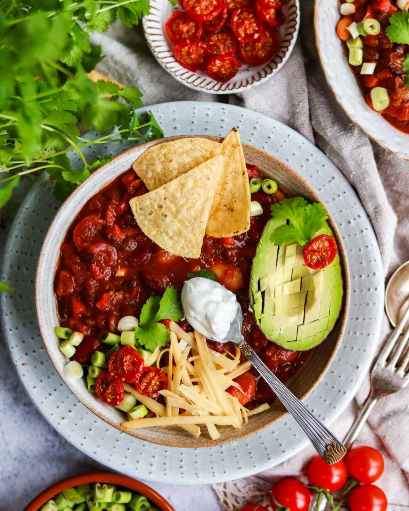 A bowl of chilli with tortilla chips, vegan cheese, vegan sour cream and an avocado on top.
