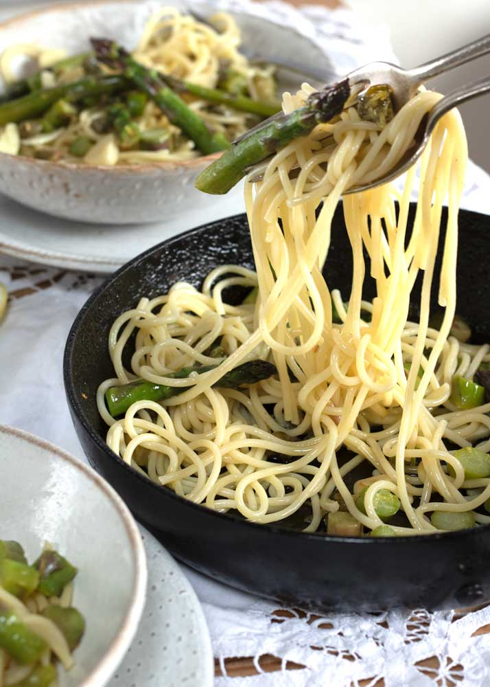 Lemon Asparagus vegan pasta being lifted from the pan