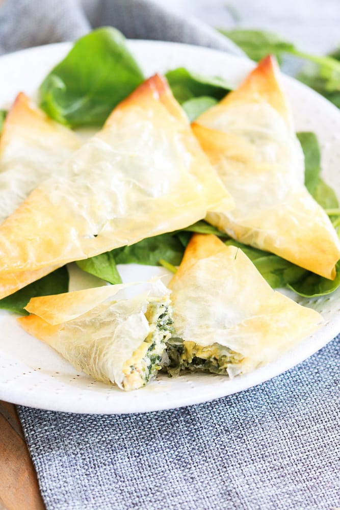 A plate of cheezy spinach triangles