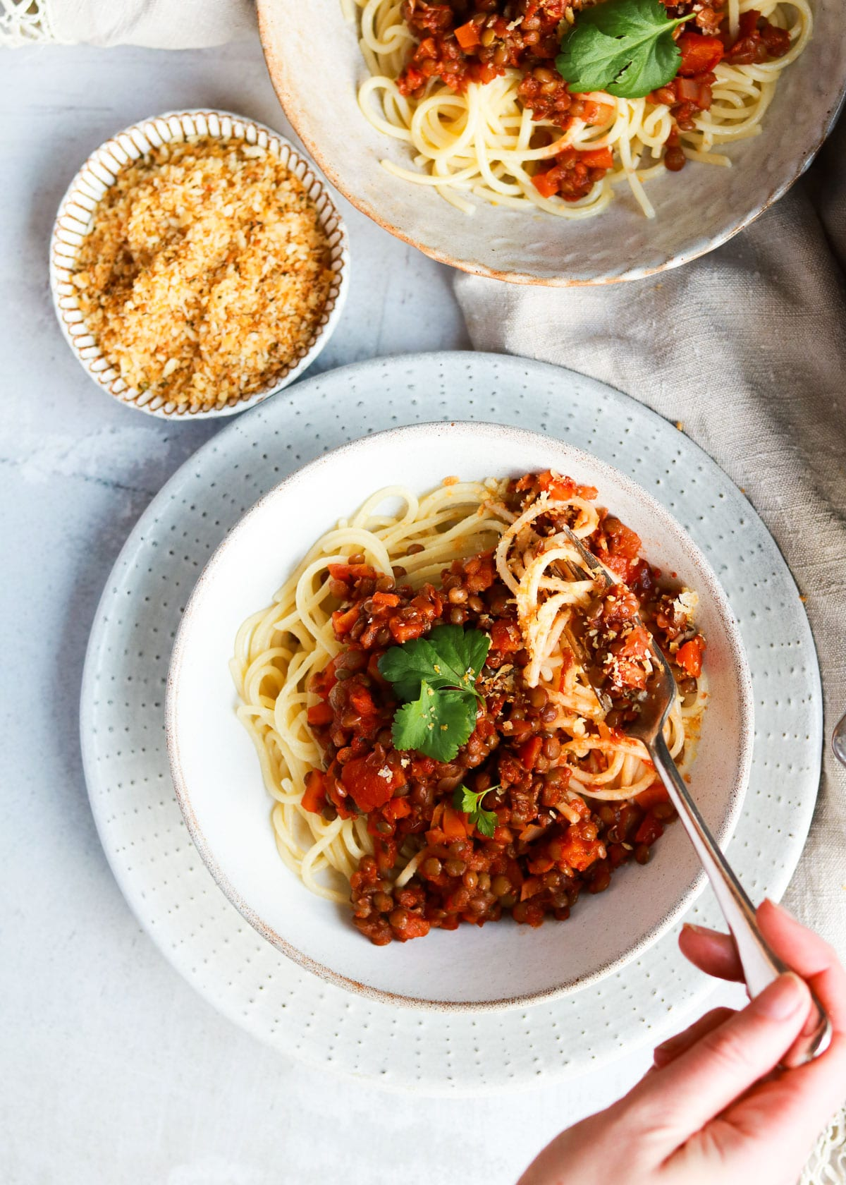 Lentil Bolognese being scooped up with a fork.