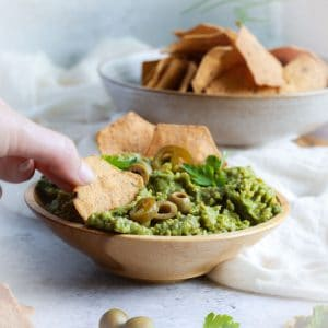 Avocado and olive dip in a bowl with a hand picking up a cracker and scooping up the dip.