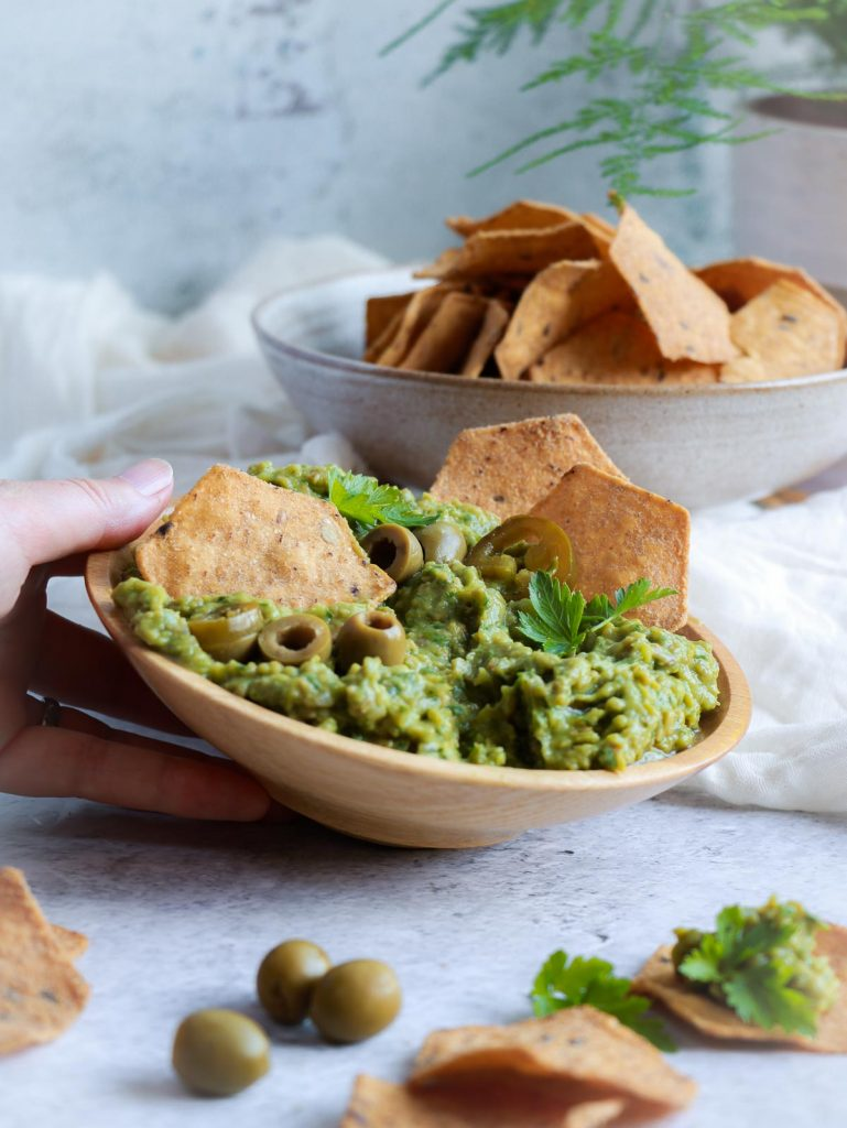 A hand placing the avocado dip on the table. There are crackers in the background.