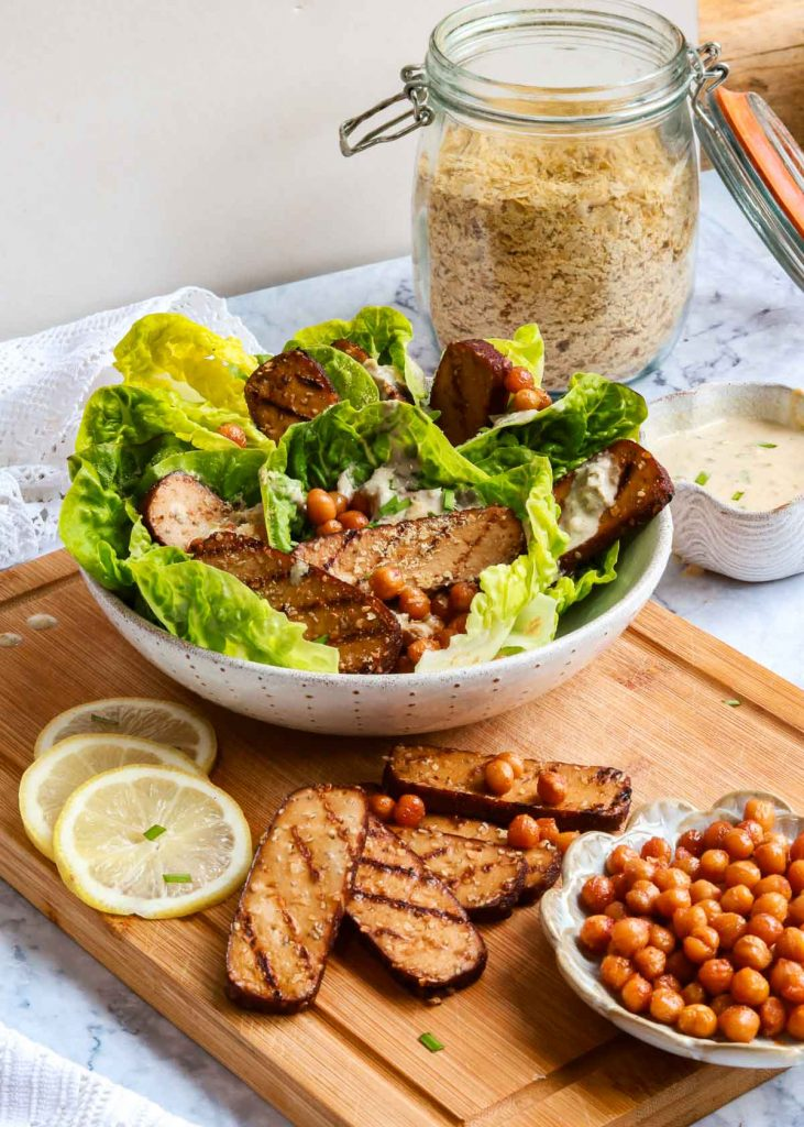 Caesar salad in a bowl with extra smoked tofu.