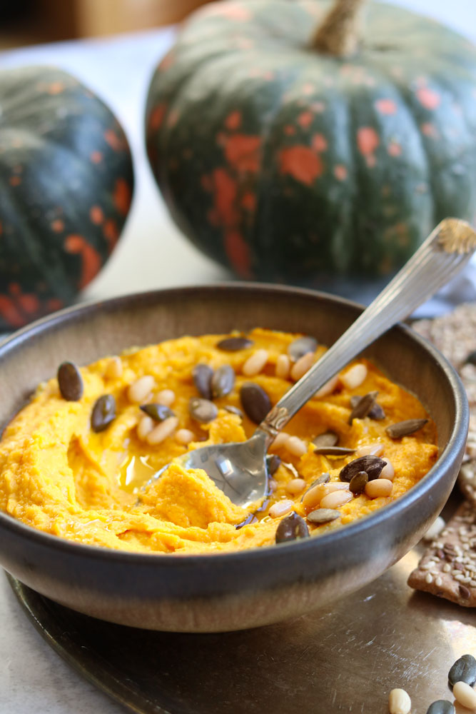 Spiced Pumpkin Hummus with a teaspoon and pumpkins in the background