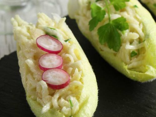 Vegan celeriac remoulade with baby radish slices in a chicory leaf