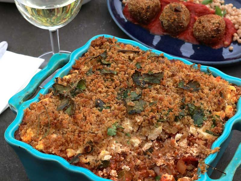 Vegan Greek style 'Feta' casserole in a blue dish on a table with wine and side dish in the background