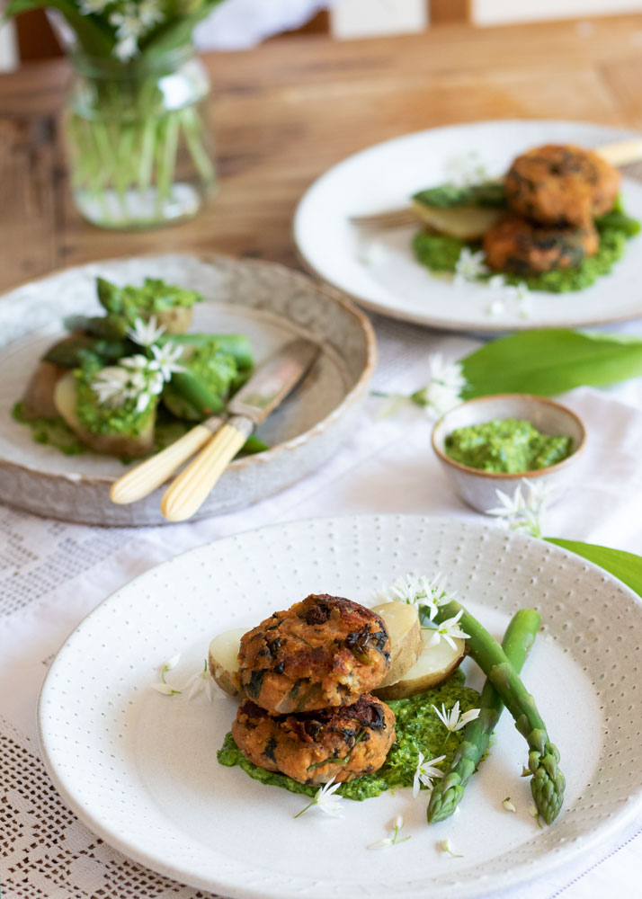 Herb Infused Lentil Cakes on a plate with Asparagus, potatoes and wild garlic pesto on a table with other dishes