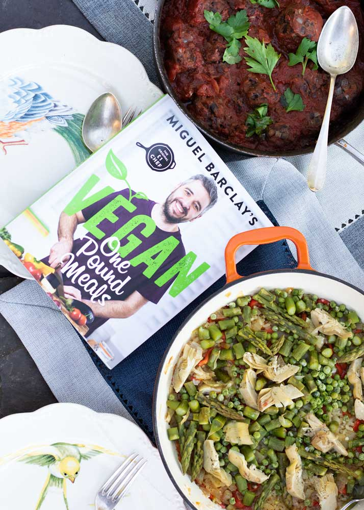 One Pound Vegan Meals book with Paella and Black Bean Balls on a table
