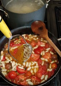 Cannellini Beans and tomatoes cooking in a pan
