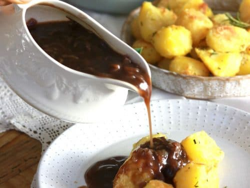 Vegan Roast Potatoes and Gravy on a plate with gravy being poured over