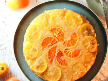 Citrus Cake on a plate, decorated with slices of orange and lemon ready to cut.