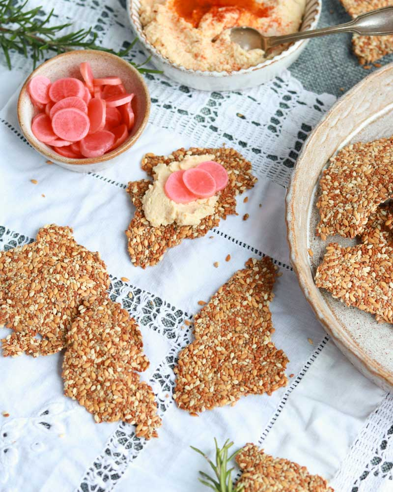 Super Seedy crackers on a plate with hummus