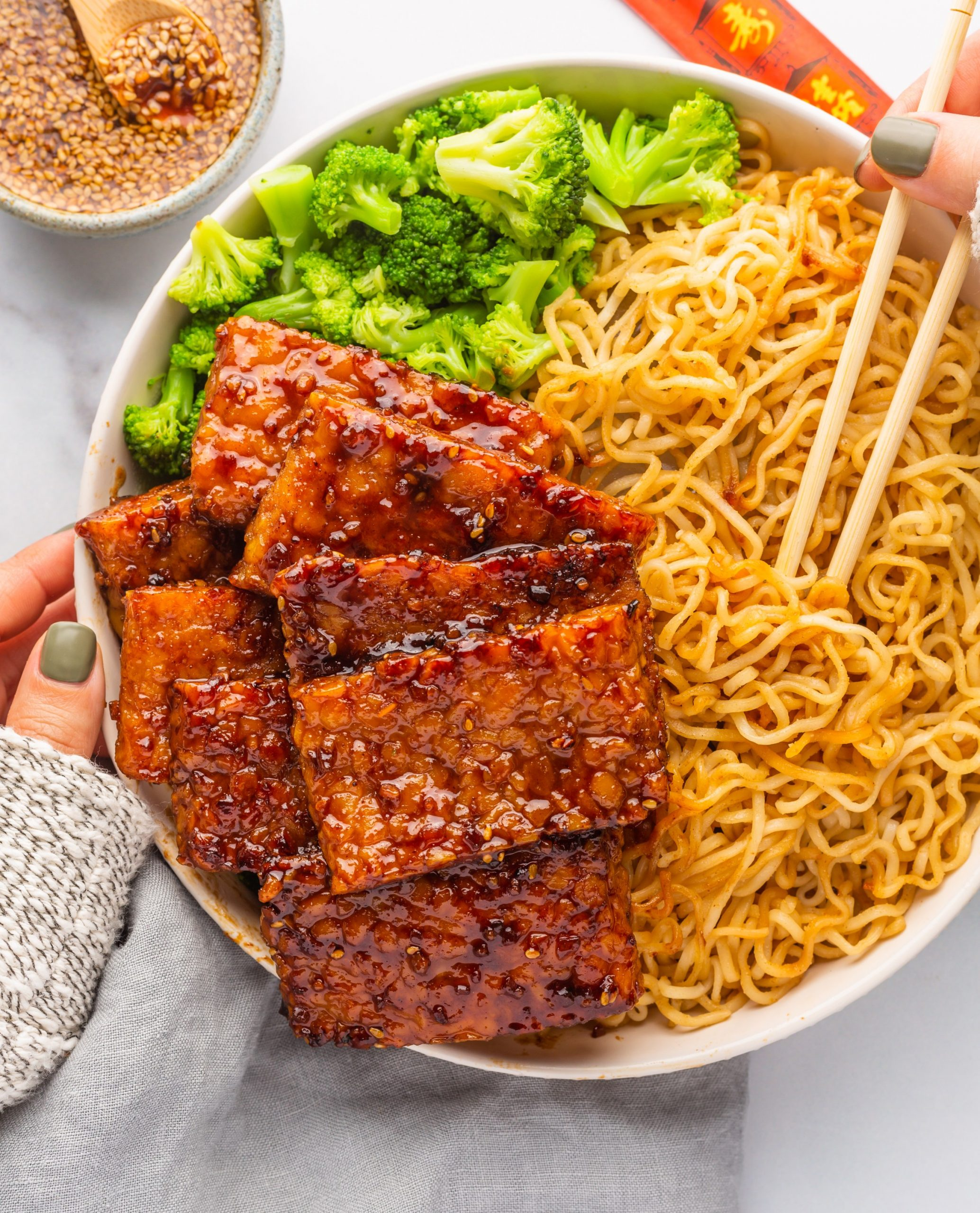 Glazed tempeh on a bed of noodles with broccoli in a bowl
