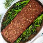 Vegan lentil and seed nutless roast on a plate surrounded by purple sprouting broccoli