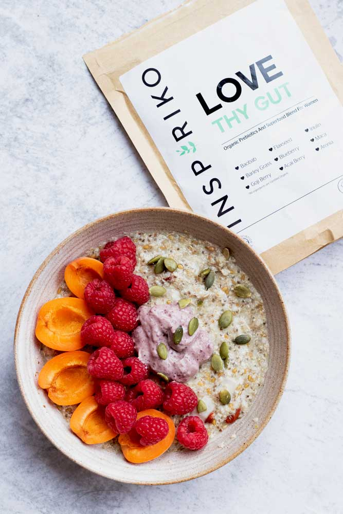 Vegan breakfast bowl topped with fruit and yoguurt and Inspiriko's gut health blend
