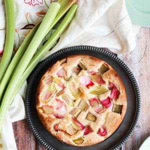 Vegan Rhubarb Cake on a plate with some rhubarb next to it