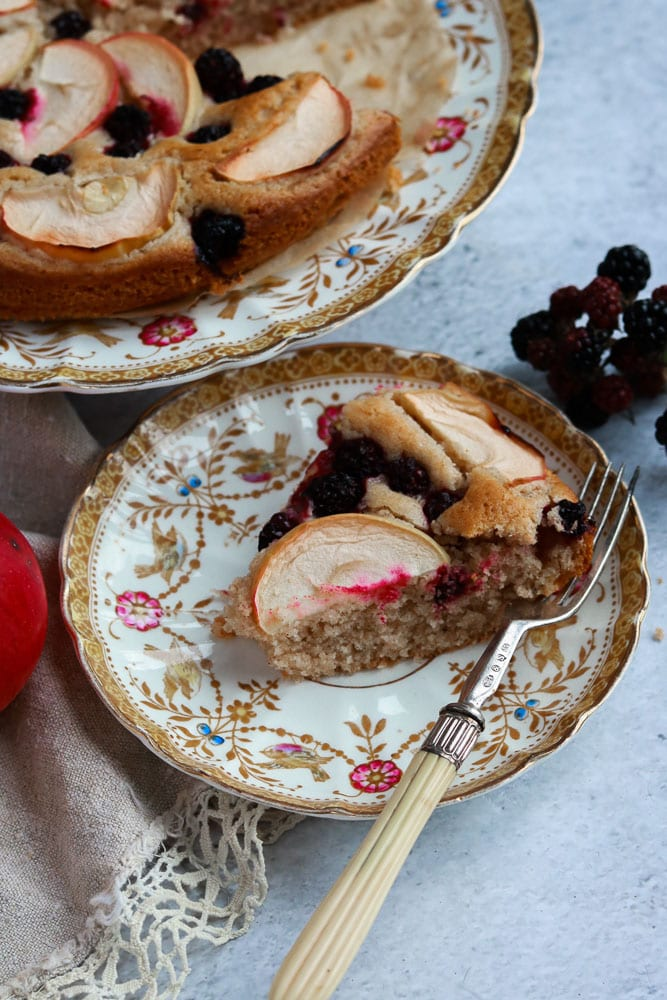 A slice of the Apple & Blackberry cake on a plate
