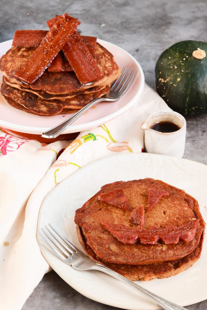 Pumpkin pancakes on a plate with facon in the shape of a face