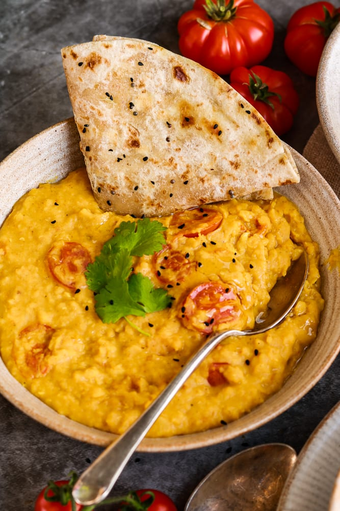 Close up of Dal with a spoon and roti.