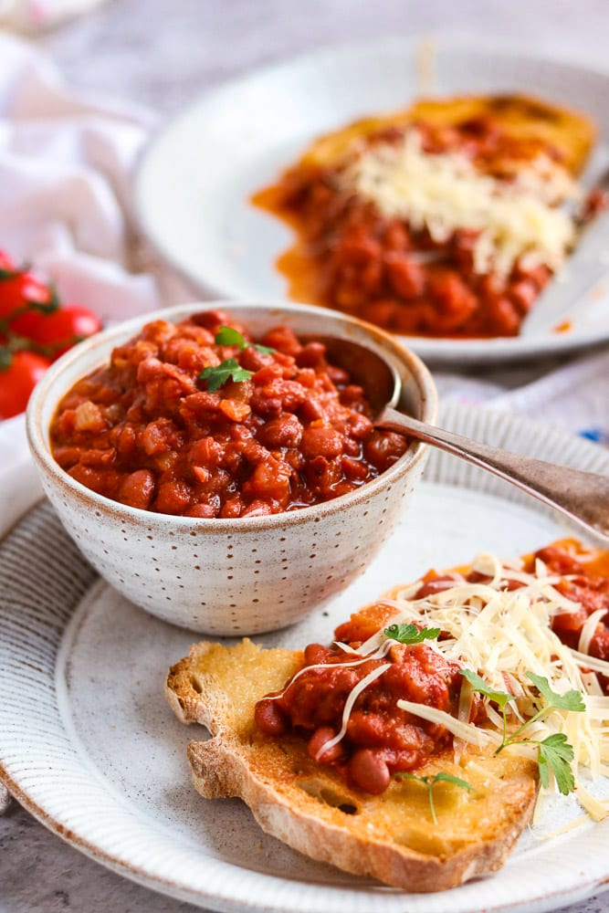 A bowl of vegan baked beans with a spoon in it