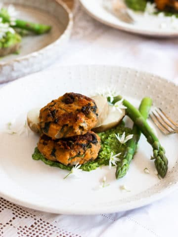 Herby Lentil Cakes on a plate with asparagus.