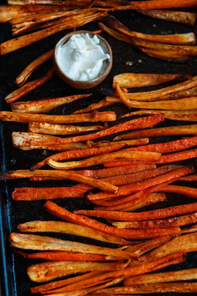 Parsnip and carrot fries on a baking sheet with alioli.