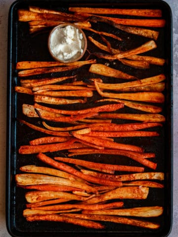 Image of parsnip and carrot fries on a tray with some vegan mayo.