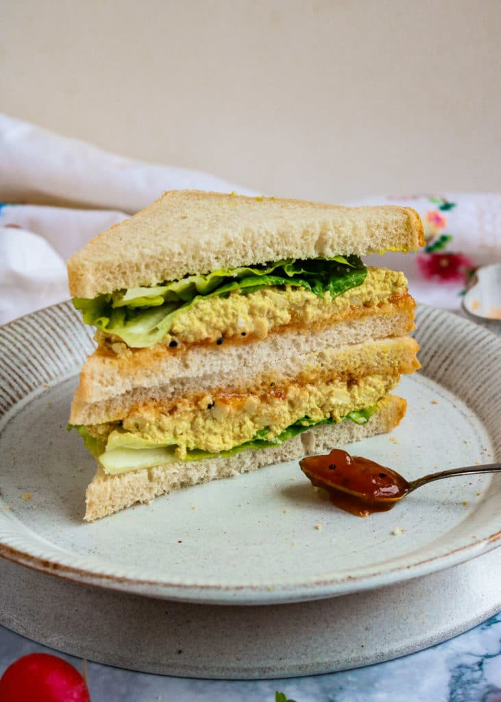 Vegan Curried Egg salad sandwich on a plate with some mango chutney.