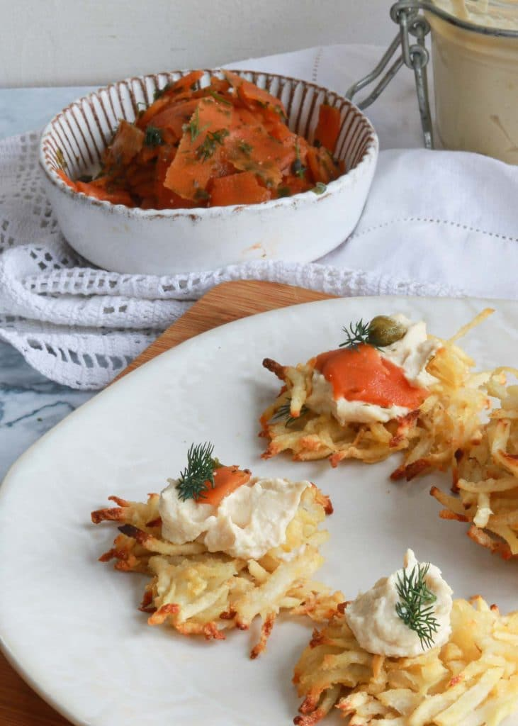 Smoked carrot lox piled on top of latkes with vegan cream cheese