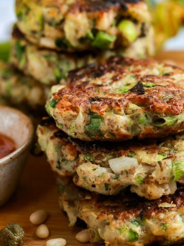 Vegan courgette fritters in a stack with some sweet chilli sauce.