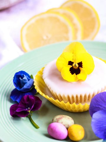 Vegan Lemon Cupcakes with a flower on top on a plate.