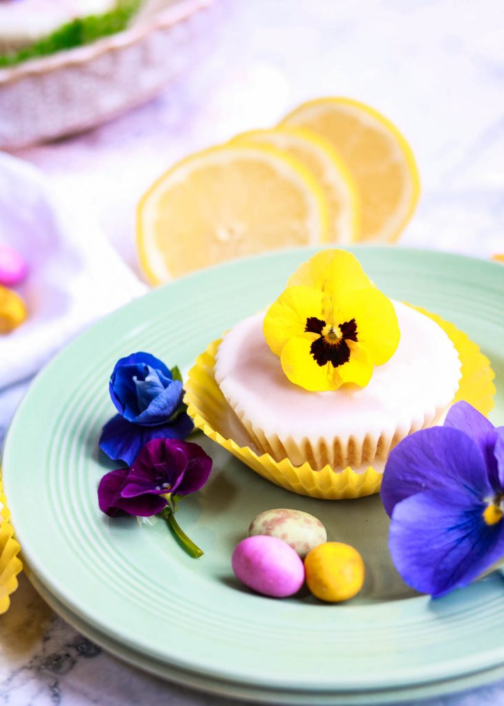 A little lemon glazed cupcake on a plate with a viola flower on top.