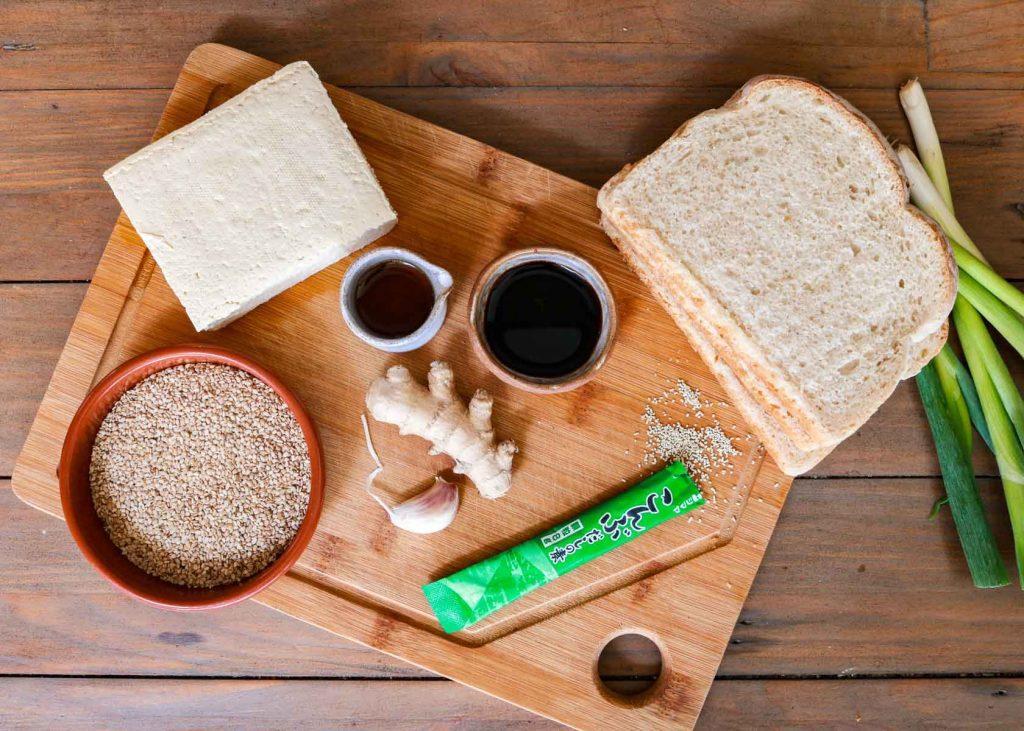 Ingredients for the Vegan Prawn Toasts laid oud.Tofu, white bread, garlic, ginger, sesame oil, soy sauce,konbu granules and sesame seeds.