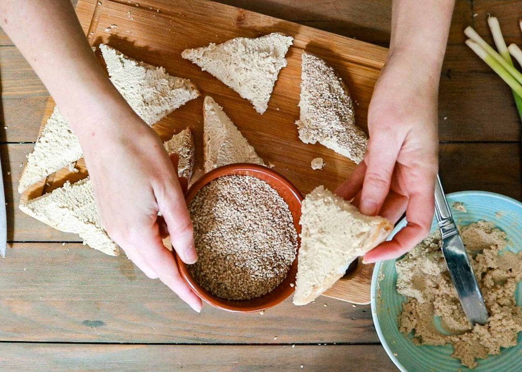 Image showing how to dip the toasts into the sesame seeds.