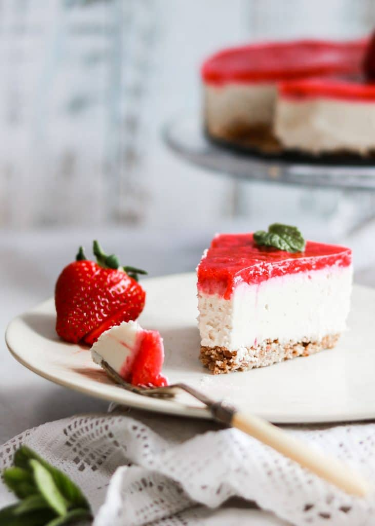 slice of vegan lemon and strawberry cheesecake on a plate