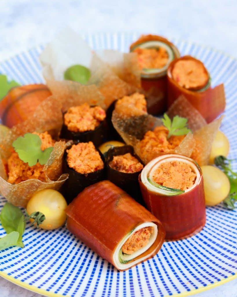 Spicy Macadamia canapes and rolls on a plate.