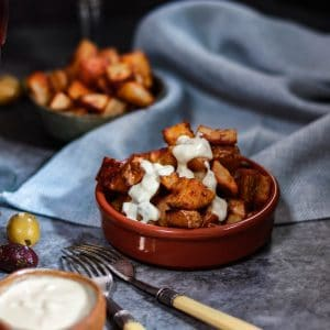 Oven baked Patatas Bravas in a tapas bowl with alioli.