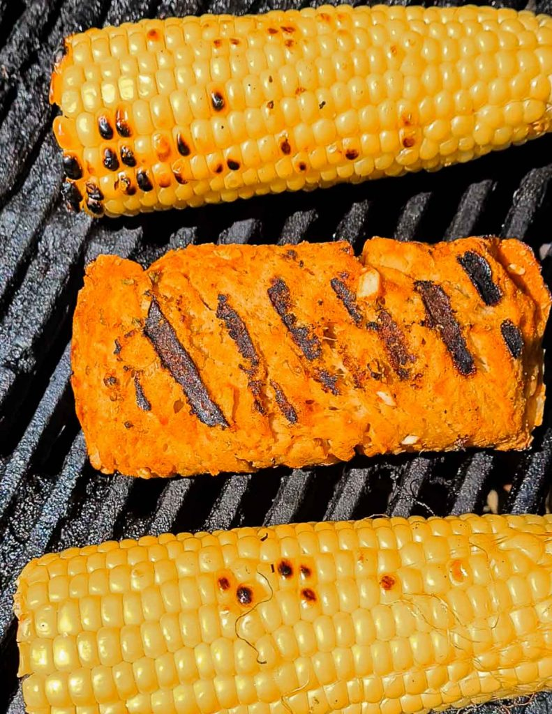 Image showing the seitan chicken fillet on a BBQ with grill marks on it. There are 2 corn on the cobs next to it.