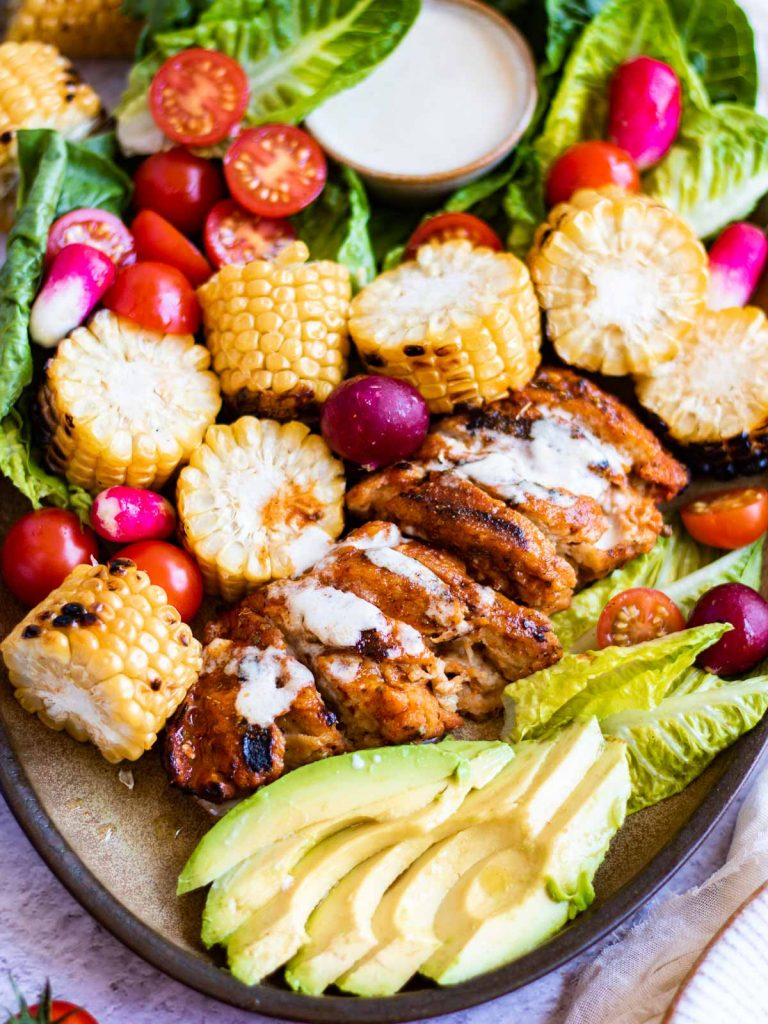 A big platter of salad, with tahini dressing in the top, and grilled sweet corn, surrounding a fillet of vegan 'chicken' (seitan) that has been marinaded in peri peri and grilled on the BBQ.
