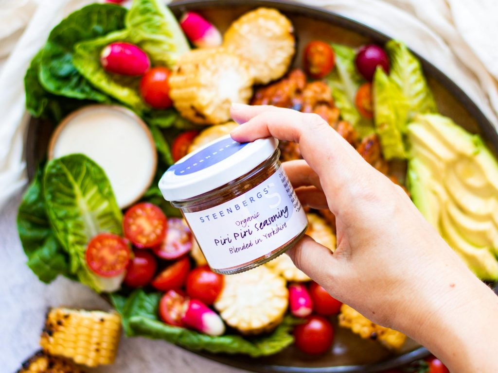 A hand holding a jar of the Steenbergs Piri Piri spice mix, over the platter of salad and vegan seitan chicken.