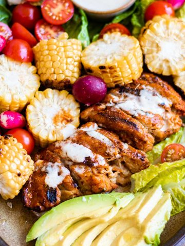 Plate of vegan peri peri chicken cut up with bbq corn on the cob and salad around it.