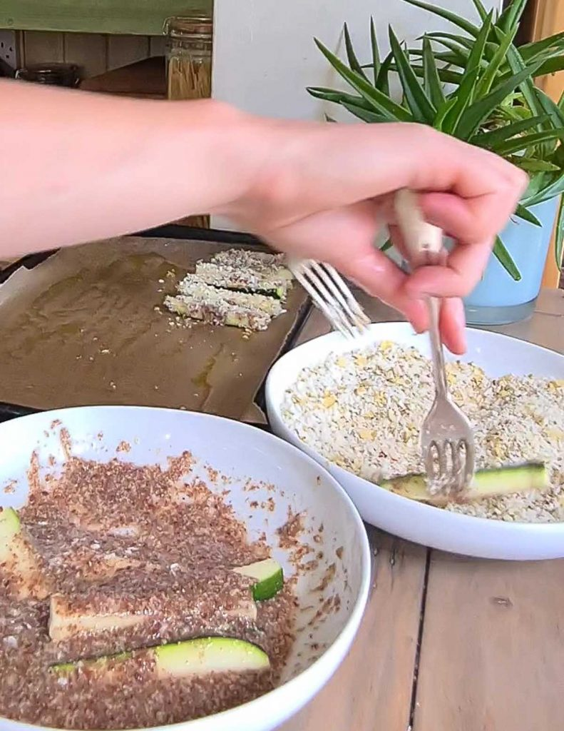Showing how to coat the zucchini fries in the crunchy breadcrumbs.
