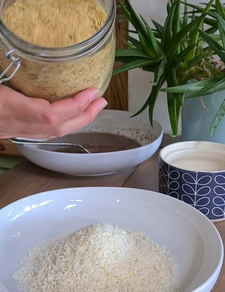 Hands pouring Nutritional Yeast into a bowl of breadcrumbs.