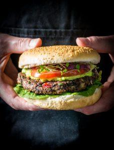 vegan burger in a bun held by hands