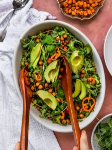Chickpea salad with quinoa and argula in a bowl with wooden salad servers