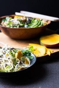 mango avocado noodle salad in a bowl with slices of mango