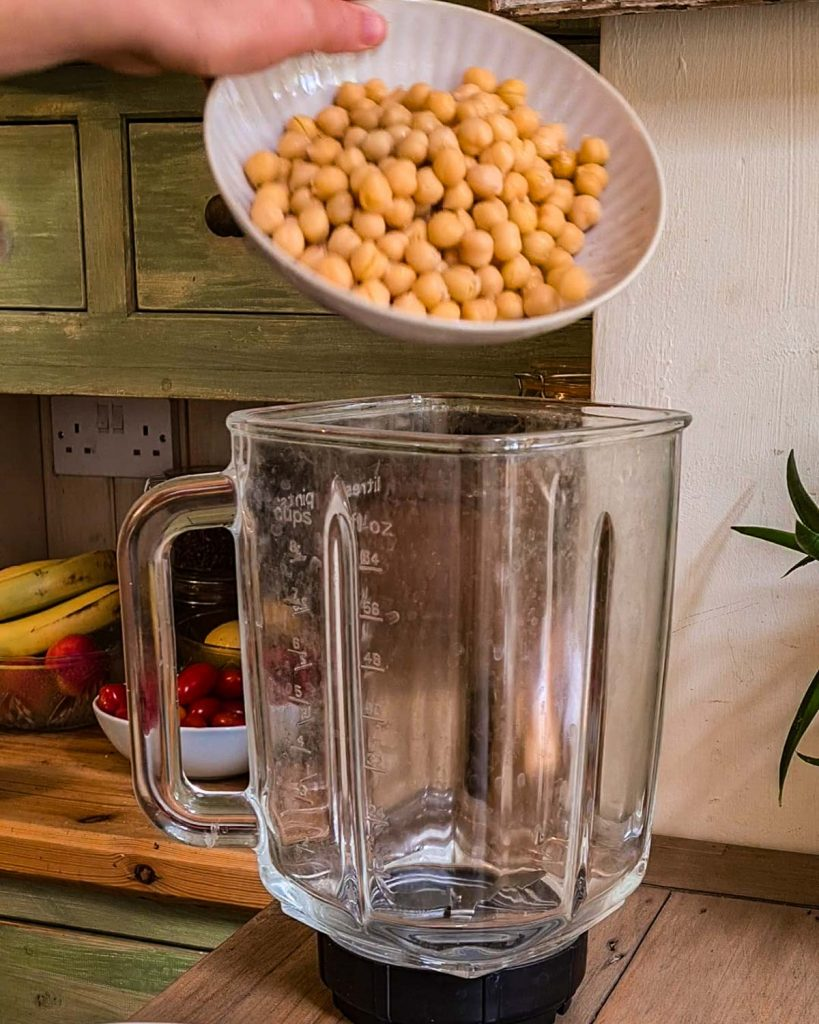 A bowl of chickpeas being added to the blender.
